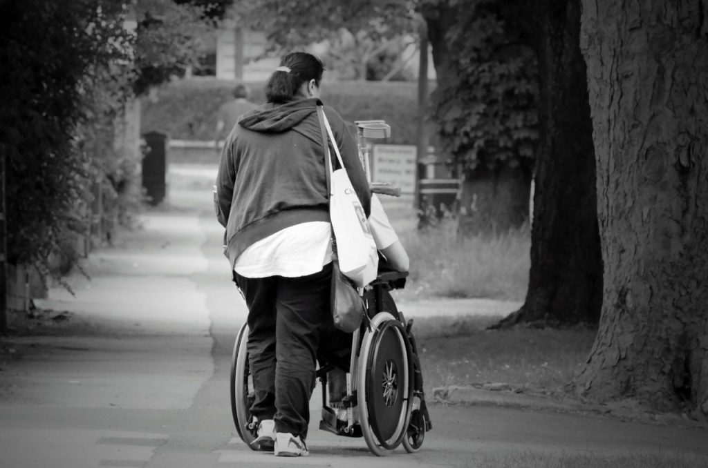 this image shows a caregiver providing the elderly with a  nice walk